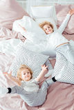 Small brothers lying in bed. Having fun Royalty Free Stock Photos