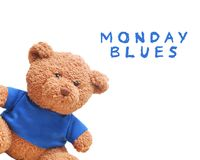 Small bear wear a blue shirt isolated with white background. Typo word `Moday Blues` royalty free stock photo
