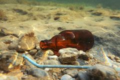 Small brown beer bottle and blue plastic straw on sandy sea bottom. Underwater photo, ocean littering concept. royalty free stock photography