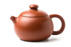 Small brown earthenware teapot with closed lid isolated on white stock image