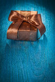 Small brown gift box on old blue painted wooden Royalty Free Stock Image