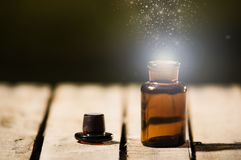 Small brown medicine bottle for magicians remedy, animated star dust coming out from top ,sitting on wooden surface.  Royalty Free Stock Photo
