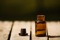 Small brown medicine bottle for magicians remedy, black cap lying next to it on wooden surface.  Stock Image
