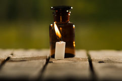 Small brown medicine bottle for magicians remedy and white wax candle sitting on wooden surface, beautiful night light. Setting, magic concept Stock Photo