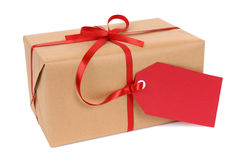 Small brown paper parcel or gift tied with red ribbon and gift tag label isolated on white background Stock Photo
