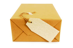 Small brown paper parcel or package with blank label isolated on white background, end view Royalty Free Stock Image