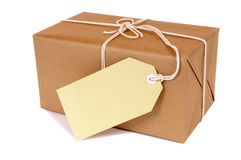 Small brown parcel package, blank label, isolated white background Stock Image