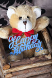 Small brown teddy bear with happy birthday sign. Brown teddy bear with happy birthday sign Royalty Free Stock Image