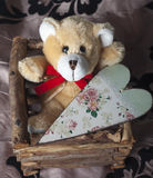 Small brown teddy bear with vintage heart. Small brown teddy bear with vintage wooden heart Royalty Free Stock Photos