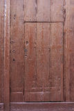 Small brown wooden door cut out of much larger one. In entrance to medieval building stock image
