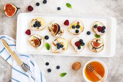 Small bruschetta with berries, honey, ricotta and mint Stock Image