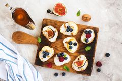 Small bruschetta with berries, honey, ricotta and mint Royalty Free Stock Photo