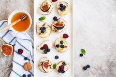 Small bruschetta with berries, honey, ricotta and mint Royalty Free Stock Photography