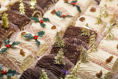 Small buches de Noël with gold decorations at pastry shop Royalty Free Stock Image