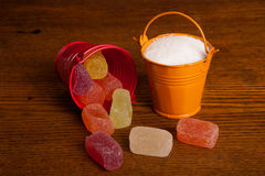Small bucket with candy and sugar on wood background Royalty Free Stock Photos