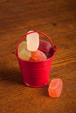 Small bucket with candy on wood background Royalty Free Stock Photo