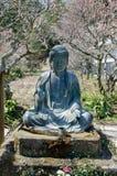 Small Buddha statue on blooming sakura background. Kamakura. Japan royalty free stock photos
