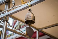 The small Buddhism religious bell. Closeup shot of iron bells hanging in temple. The small Buddhism religious bell. Closeup shot of iron bells hanging in Wat stock images