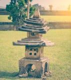Small Buddhism stone shrine pagoda in garden. Royalty Free Stock Photo