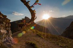 Small buddhist monastery with prayer flags and sun rays during sunset Stock Image