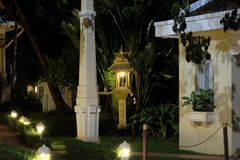 A small Buddhist sanctuary near a tropical plant. Many small lanterns illuminate the walkways.  royalty free stock photography