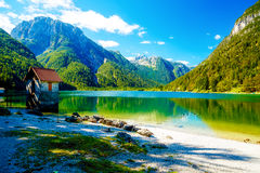 Small building at a beautiful lake surrounded by stunning mountain landscape. Royalty Free Stock Photography