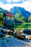Small building at a beautiful lake surrounded by stunning mountain landscape. Royalty Free Stock Images