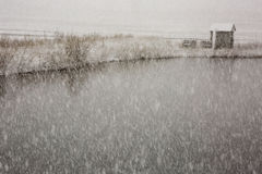 A small building on a pond during a snowstorm Stock Photography