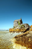 The small building on sea brink in low tide Stock Photography