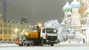 Small bulldozer loads 1st wet snow to trucks on Red Square stock video