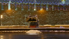 Small bulldozer loads 1st wet snow to trucks on Red Square stock footage