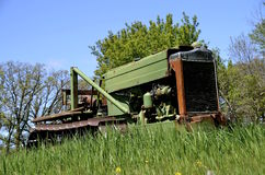Small bulldozer parked in the long grass Stock Image