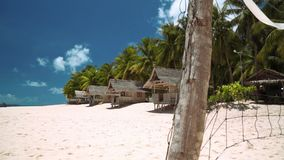 Small bungalows on white sand beach on tropical island, volleyball net stock video footage