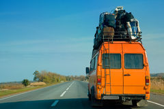Small bus. Orange bus with luggage on the open road Stock Photos