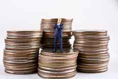 Small Business. Miniature businessman standing on stacks of quarters Stock Photos