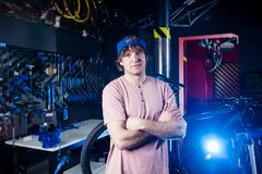 Small business and bicycle transport service. Portrait of a young man in a cap posing against the backdrop of a bicycle workshop a. Nd a tool for setting up and royalty free stock images