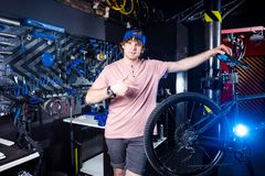 Small business and bicycle transport service. Portrait of a young man in a cap posing against the backdrop of a bicycle workshop a. Nd a tool for setting up and royalty free stock photo