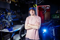Small business and bicycle transport service. Portrait of a young man in a cap posing against the backdrop of a bicycle workshop a. Nd a tool for setting up and royalty free stock photos