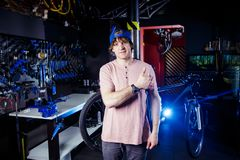 Small business and bicycle transport service. Portrait of a young man in a cap posing against the backdrop of a bicycle workshop a. Nd a tool for setting up and stock photos