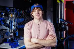 Small business and bicycle transport service. Portrait of a young man in a cap posing against the backdrop of a bicycle workshop a. Nd a tool for setting up and stock photo