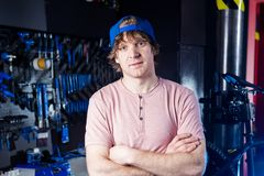Small business and bicycle transport service. Portrait of a young man in a cap posing against the backdrop of a bicycle workshop a. Nd a tool for setting up and royalty free stock photography