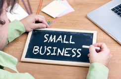 Small Business. Chalkboard on wooden office desk Stock Photos