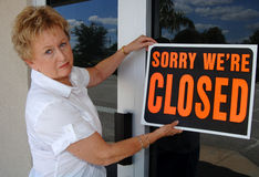 Small business closing. An unhappy senior woman hanging a closed sign in front of business out of business Royalty Free Stock Photos