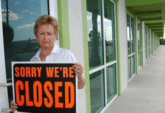 Small business closing. An unhappy senior woman holding a closed sign in front of business Stock Image