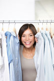 Small business clothing shop owner. Portrait in store. Funny image of woman clothes shop owner peeping through shirts smiling happy and excited at camera Royalty Free Stock Photos