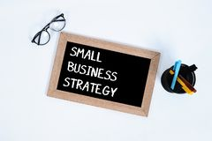 Small Business / Conceptual. Top view of SMALL BUSINESS STRATEGY text written on blackboard for business with glasses, marker and royalty free stock photos