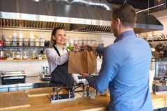 Small business and entrepreneur concept with smiling young waitress wearing black apron serving customer at counter in restaurant. Small business and stock photos