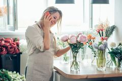 Small Business Flower Shop Owner. using phone to take orders for her store stock photo
