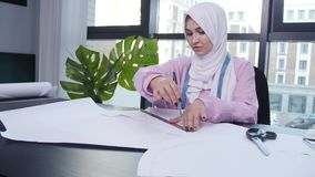 Small business and hobby concept. Muslim woman fashion designer pinning paper pattern at the table in tailor shop.  stock footage
