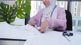 Small business and hobby concept. Muslim woman fashion designer pinning paper pattern at the table in tailor shop.  stock video footage